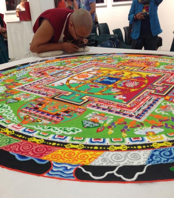 A Tibetan monk creating a mandala sand painting